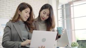 2 азиатских молодых творческих коммерсантки держа чашку кофе, работающ на компьтер-книжке и disscuss о работе пока работающ в офи