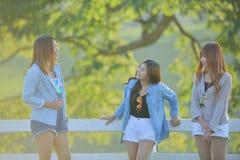 3 азиатских молодых ladys наслаждаются жарой после полудня в саде Стоковое фото RF