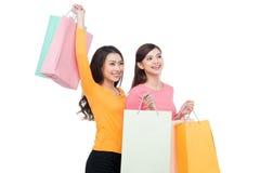 2 азиатских подруги с покупками изолированной на белизне Стоковые Изображения RF