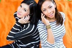 2 азиатских подруги с телефоном Стоковая Фотография RF