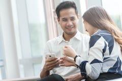 2 азиатских сотрудника используют havi работы компьтер-книжки и smartphone совместно Стоковая Фотография