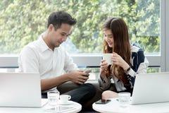 2 азиатских сотрудника используют havi работы компьтер-книжки и smartphone совместно Стоковое Изображение RF