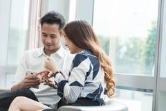 2 азиатских сотрудника используют havi работы компьтер-книжки и smartphone совместно Стоковая Фотография RF