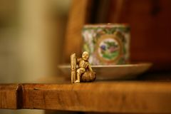 Азиатское античное stillife с чашкой цвета слоновой кости netsuke и чая стоковое фото rf