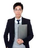 Азиатское владение бизнесмена с портативным компьютером Стоковые Изображения RF