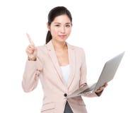 Азиатское владение коммерсантки с компьтер-книжкой и палец указывают вверх Стоковое Изображение