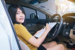Азиатское дело женщины сидя в автомобиле и делая примечание или работу Стоковое Изображение RF