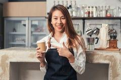 Азиатское женское владение barista чашка кофе служа к ее клиенту с улыбкой окруженному с предпосылкой счетчика бара стоковые изображения