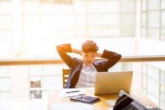 Азиатское короткое дело tomboy черных волос с рукой 2 на голове сидит Стоковая Фотография RF