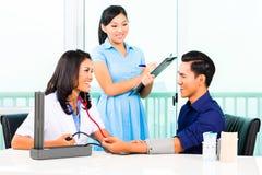 Азиатское кровяное давление проверки доктора на пациенте Стоковое фото RF