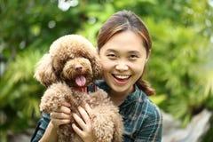 Азиатское объятие девушки с ее собакой пуделя Стоковое Изображение RF