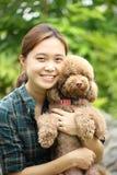 Азиатское объятие девушки с ее собакой пуделя Стоковые Фото