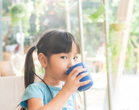 Азиатское питье ребенка девушки некоторая вода Стоковая Фотография RF