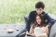Азиатское подростковое relaxingtime пар сидит возлежать на софе в стоковые фото