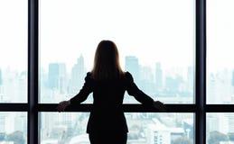 Азиатское положение бизнес-леди и смотреть вне окно на предпосылке вида на город стоковое изображение rf