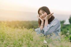 Азиатское положение женщины усмехаясь в полях зеленой травы в солнце утра со счастливой стороной стоковые фотографии rf