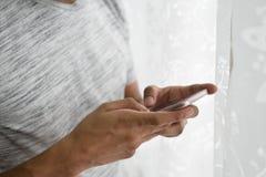 Азиатское предназначенное для подростков используя его smartphone в его комнате Стоковые Изображения