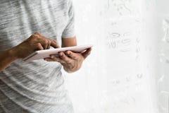 Азиатское предназначенное для подростков buzy с его таблеткой в его доме Стоковые Фотографии RF