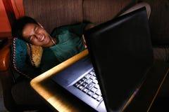 Азиатское предназначенное для подростков смеясь над и наблюдая видео на компьтер-книжке Стоковое фото RF
