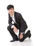 Азиатское сидение на корточках бизнесмена Стоковое фото RF