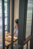 Азиатское сообщение студента отправляя СМС на умном телефоне стоковые фото