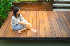 Азиатское усаживание женщины ослабляет на деревянных террасе или крылечке около пруда в саде стоковые фото