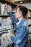 Азиатское чтение человека в библиотеке Стоковая Фотография