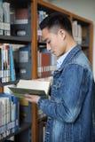 Азиатское чтение человека в библиотеке Стоковые Фото