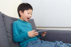 Азиатское чувство мальчика возбуждая для использования таблетки стоковая фотография rf