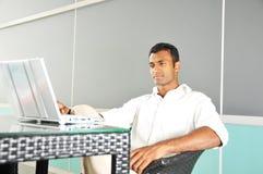азиат его индийская компьтер-книжка смотря человека outdoors Стоковое Изображение