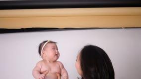Азиат мамы с длинными волосами поднимает дочь младенца акции видеоматериалы
