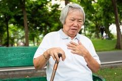 Азиат престарелый с некоторыми симптомами, затруднением дыша, страданием или проблемами сердца, связывает симптомы сердца стоковое изображение