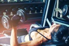 Азиат резвится женщина делая тренировки с весами гантели в спортзале Стоковое фото RF