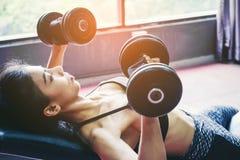 Азиат резвится женщина делая тренировки с весами гантели в спортзале Стоковое Изображение