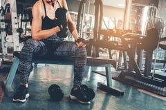 Азиат резвится женщина делая тренировки с весами гантели в спортзале Стоковые Изображения RF