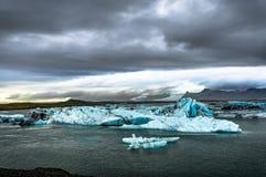 Айсберги плавая в ледниковое озеро Jokulsarlon на заходе солнца в Icela Стоковая Фотография