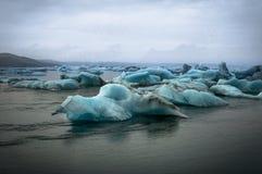 Айсберги плавая в ледниковое озеро Jokulsarlon на заходе солнца в Icela Стоковое Изображение