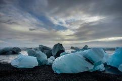 Айсберги плавая в ледниковое озеро Jokulsarlon на заходе солнца в Icela Стоковое Изображение RF
