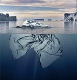 Айсберг пластмассы отброса плавая в океан с Гренландией назад стоковое фото