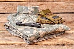 Аккуратно сложенное камуфлирование войск одевает с перчатками и факелом Стоковая Фотография