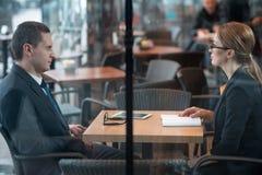 Аккуратные деловые партнеры говоря на столе в комнате Стоковое Изображение RF