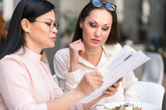 Аккуратные женщины смотря бумагу на таблице Стоковые Изображения RF