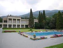 Аккуратный бассейн обеспеченный с цветочными горшками с цветками в большом дворе с лужайкой и твердым домом с балконами с Стоковое Изображение