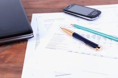 Аксессуары дела - ручка, телефон и компьтер-книжка лежа на документах налога Стоковое Фото