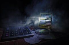 Аксессуары дела (увеличитель, калькулятор) и графики, таблицы, диаграммы на таблице с темной предпосылкой Селективный фокус Стоковые Фотографии RF