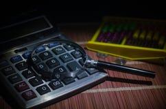 Аксессуары дела (увеличитель, калькулятор) и графики, таблицы, диаграммы на таблице с темной предпосылкой Селективный фокус Стоковая Фотография RF