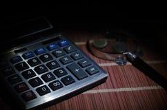 Аксессуары дела (увеличитель, калькулятор) и графики, таблицы, диаграммы на таблице с темной предпосылкой Селективный фокус Стоковое Изображение RF