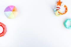 Аксессуары и игрушки младенца на белой насмешке взгляд сверху предпосылки вверх Стоковые Фотографии RF