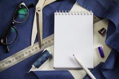 Аксессуары и инструменты портноя взгляд сверху Пустой блокнот окруженный с вырезыванием scissors, катышкы потока, фиолетовой ткан Стоковое Изображение