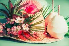 Аксессуары летнего отпуска: соломенная шляпа, пить кокоса, солнечные очки листья ладони и экзотические цветки, вид спереди стоковая фотография rf
